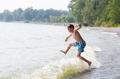 Young boy playing in the waves at a beach Stock Image