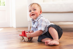 Young Boy Playing With Wooden Toy Car At Home. Smiling At Camera Royalty Free Stock Photo