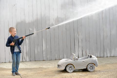 A young boy plays with a car wash hose. A young вoy plays with a car wash hose and a race prize in a rural compound in a hot summer stock image
