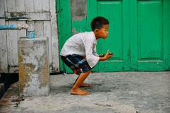A young boy plays with his phone in Mandalay. stock images