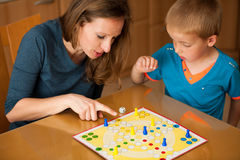 Young boy plays ludo game with his mother on a table in livingro Royalty Free Stock Photo