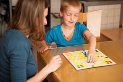Young boy plays ludo game with his mother on a table in livingro Royalty Free Stock Photos