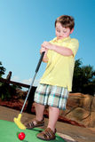 Young boy plays mini golf Royalty Free Stock Image