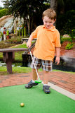 Young boy plays mini golf Stock Photo