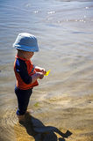 Young boy plays at the ocean tide. Royalty Free Stock Photos