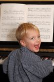 Young boy plays piano. Portrait of a happy young boy playing piano Royalty Free Stock Images