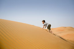 Young boy plays among sand dunes in desert Royalty Free Stock Photos