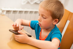 Young boy plays with a smart phone at kitchen table Stock Photography