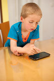 Young boy plays with a smart phone at kitchen table Stock Image
