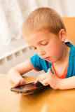 Young boy plays with a smart phone at kitchen table Royalty Free Stock Images