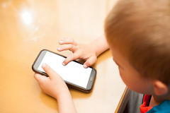 Young boy plays with a smart phone at kitchen table Stock Photos
