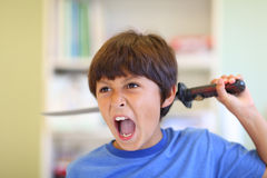 Young boy plays with toy sword Stock Images