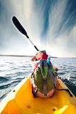 Young boy plows through the waters of the sea with his canoe. Boy plows through the waters of the sea with his canoe Royalty Free Stock Images