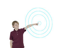 Young boy pointing to digitally designed concentric circles over white background Stock Photo