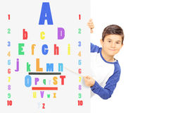 Young boy pointing with wooden stick on colorful eyesight test Stock Images