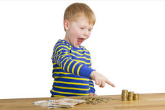 Young boy poits to money towers Royalty Free Stock Photo