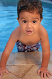 Young boy in pool. A young boy looks at the camera as he has fun in the pool stock photos