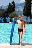 Young boy at a pool. Young smiling pretty boy with surf board at a pool Stock Images