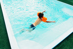 Young Boy in Pool with Floaties Royalty Free Stock Images