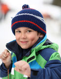 Young boy portrait. 6 year old smiling and showing fist wearing winter clothes Royalty Free Stock Photo