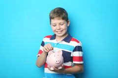 Young boy. Portrait of young boy with piggy bank on blue background Stock Photo