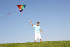 Young boy poses with kite in a field Stock Images