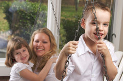 Young Boy Poses with Mom and Sister. Young Boy Smiles for The Camera as His Mom and Sister Look On Stock Image