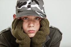 Young boy pouting while holding face in gloves. Young boy in jacket, brown gloves and gray camouflage hat holding his pouting face in hands Stock Images