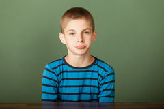 Young boy is in the pouts. Portrait of upset sulking young boy showing his displeasure by sitting at desk against green chalkboard background Stock Photography