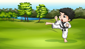 A young boy practicing karate near the river Royalty Free Stock Photo
