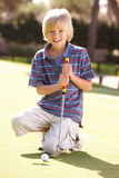 Young Boy Practising Golf. On Putting On Green Royalty Free Stock Photos