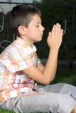 Young boy praying outdoors Stock Photo