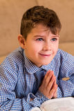 Young boy praying and smiling. Royalty Free Stock Photography
