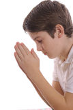 Young boy praying on white vertical. Shot of a young boy praying on white vertical Royalty Free Stock Image