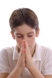 Young boy praying on white vertical center. Shot of a young boy praying on white vertical center Stock Photography