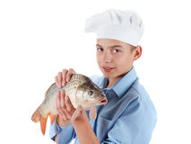 Young boy prepare a fish carp on white background Stock Image