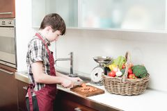 Young boy prepare vegetables over the bench stock images