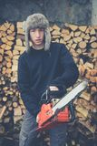 Young boy prepares firewood with chainsaw Stock Images