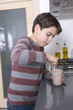 Young boy preparing a glass of milk Stock Images