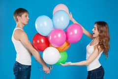Young boy presenting baloons to a girl. Stock Photos
