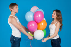 Young boy presenting baloons to a girl Stock Photos