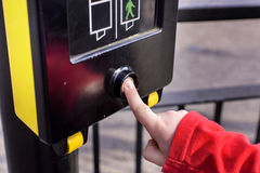 Young boy pressing the button to a PELICON crossing. Close up shot of young boy pressing the button to a PELICON crossing. PELICON stands for Pedestrian Lights royalty free stock photos