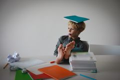 Young boy pretend doing homework relaxed at home. Difficult learning stock photos