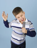 Young boy pretending rock star. Young boy dancing and singing into a hair brush pretending to be a rock star royalty free stock photography