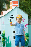 Young Boy Pretending To Be Workman Outside Palyhouse Stock Images