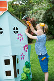 Young Boy Pretending To Fix Cardboard Playhouse Stock Images