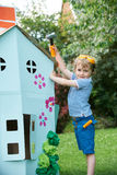 Young Boy Pretending To Fix Cardboard Playhouse Royalty Free Stock Image