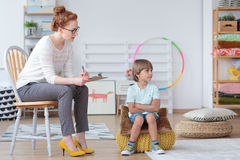 Young boy during psychotherapy session. Young boy sitting on yellow pouf refusing to listen to his psychotherapist during session in a classroom royalty free stock photos