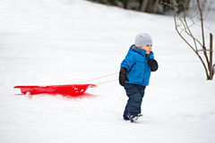 Young Boy Pulling a Sled in the Snow Stock Photos