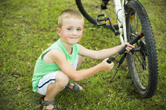 Young boy pumping th� bicycle tube Stock Images
